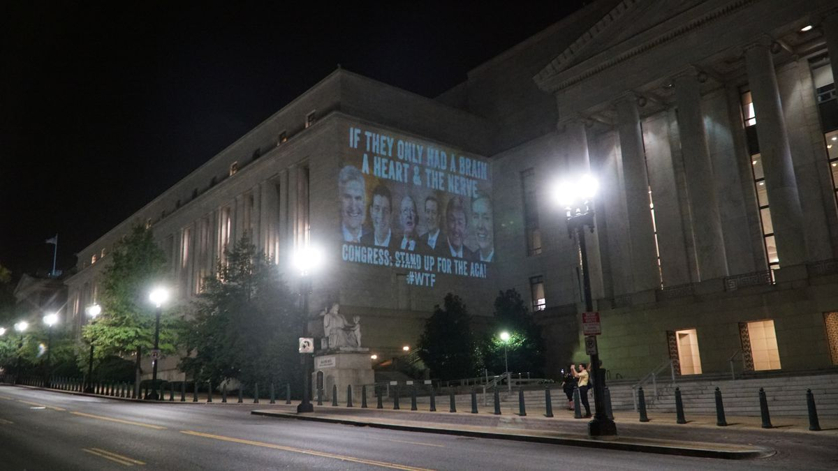 An ad by WTF defending Obamacare, projected onto a House office building