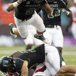 Hawaii defenders Charles Clay, middle, and Bubba Poueu-Luna scramble to recover a fumble by Lamar defensive back Mike Venson during the first half of an NCAA college football game, Saturday, Sept. 15, 2012, in Honolulu.