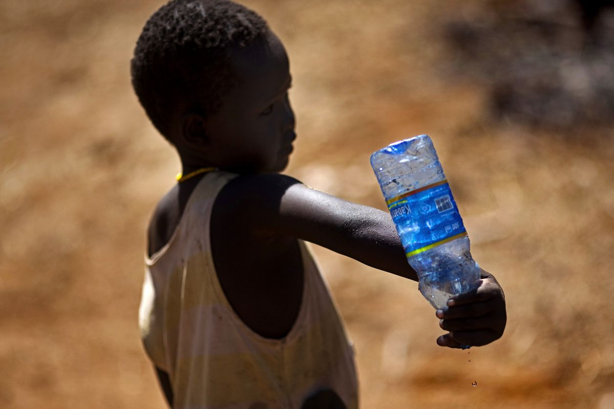 A child holds a water bottle during a water shortage in Kenya.