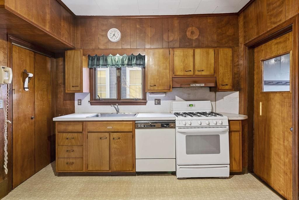 An older kitchen with one counter and lots of wood paneling.