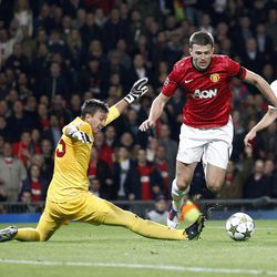 Manchester United's Michael Carrick, right, gets round Galatasaray's goal keeper Fernando Muslera, left, to score the first goal of the game for his side during their UEFA Champions League soccer match at Old Trafford in Manchester, England, Wednesday Sept. 19, 2012.