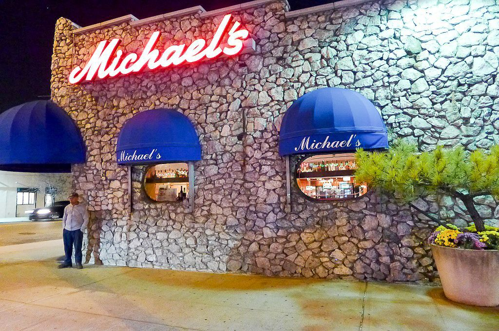 """A stoned building has a red glowing neon sign saying """"Michael's"""""""