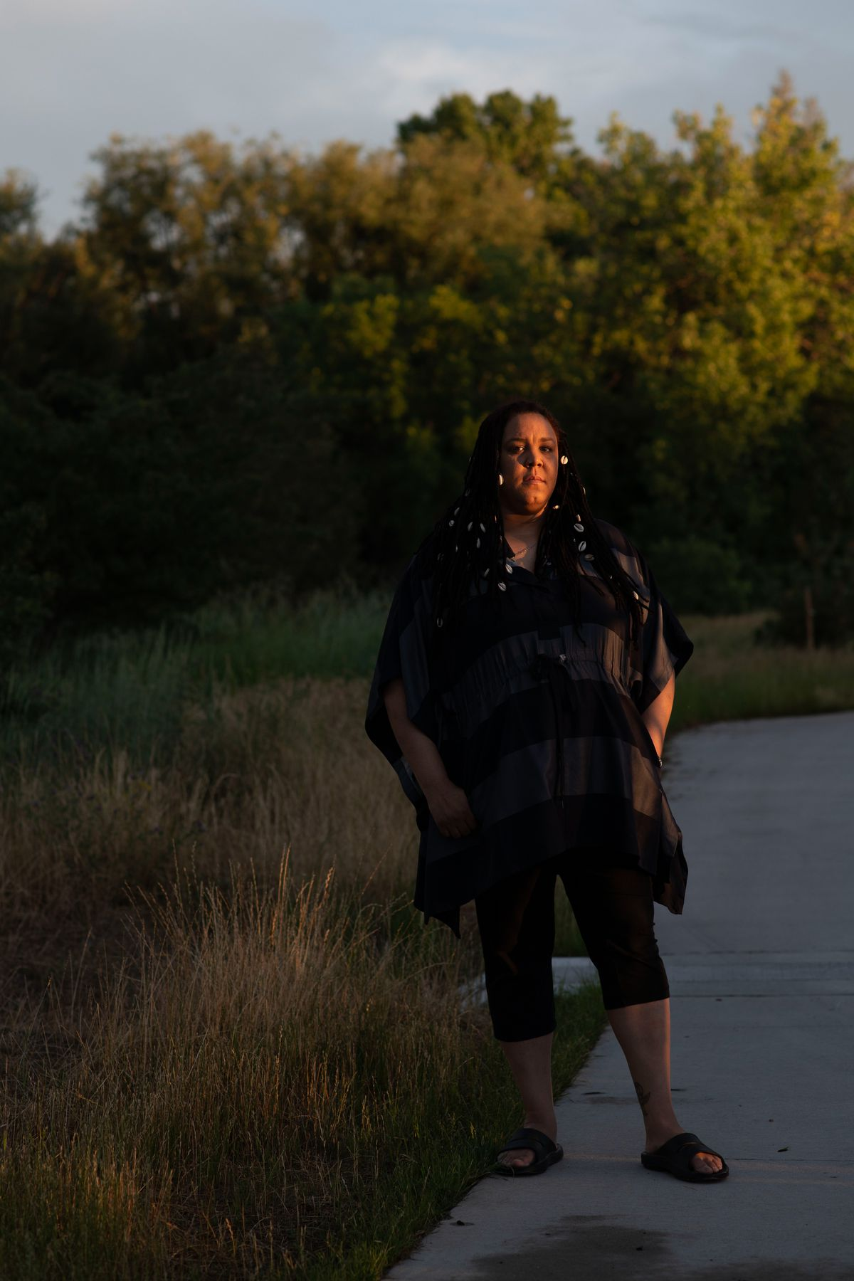 A Black woman stands on a sidewalk in a park. She is looking into the distance, and there is warm sunlight reflected on her face.