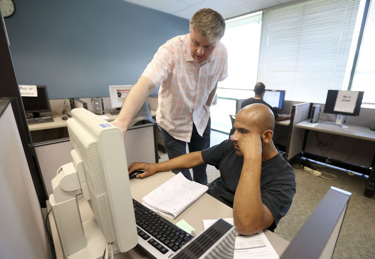 Stephen Cashon, an employment counselor with the Utah Department of Workforce Services, helps Juan Rodriguez apply for a new ID so that he can apply for jobs at the department's offices in Salt Lake City on Tuesday, June 22, 2021.