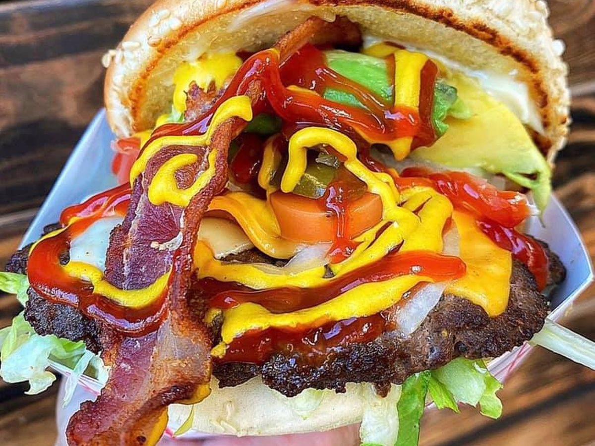 A giant burger stuffed with bacon, avocado, peppers, onion, shredded lettuce, with ketchup and mustard on a sesame seed bun. The burger is so stuffed with toppings it looks like it's in danger of everything spilled out of it