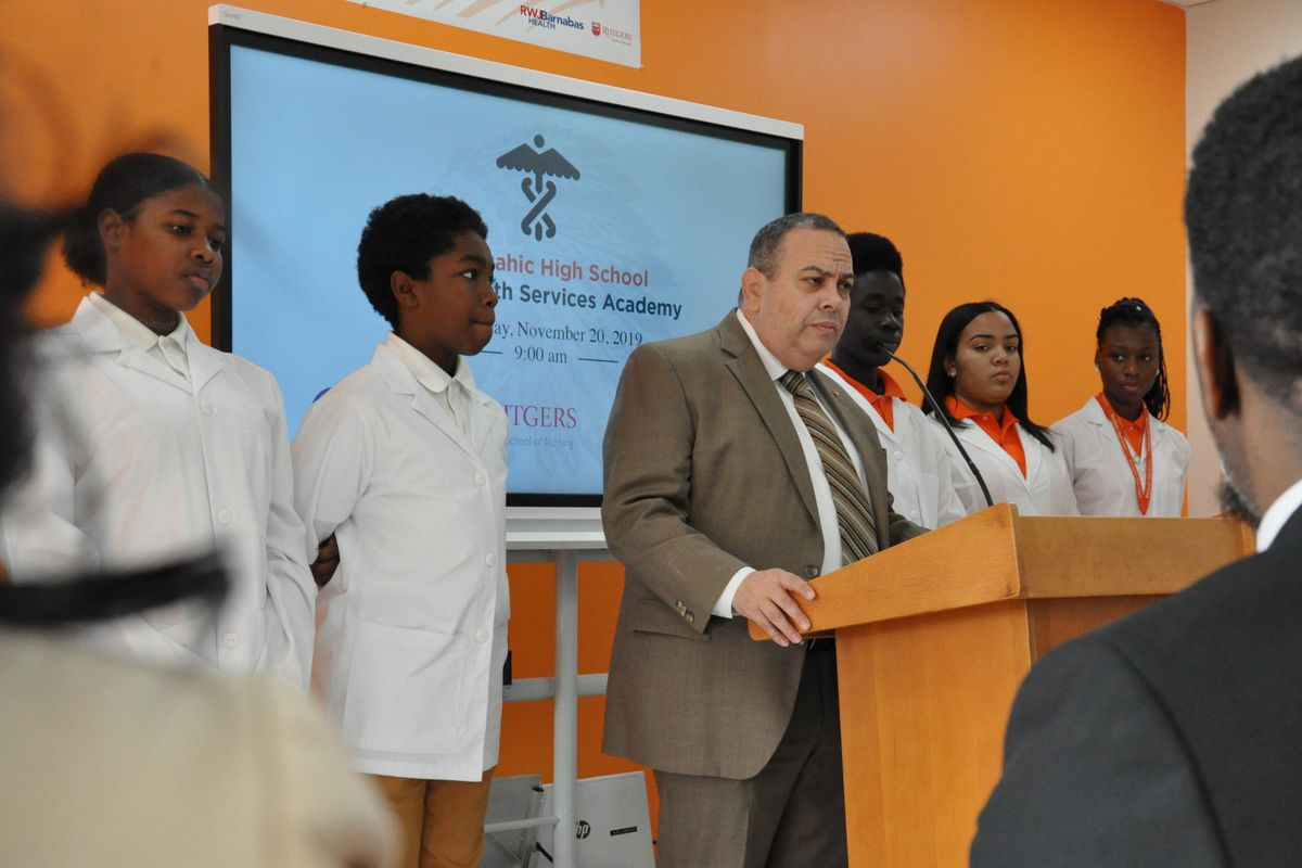 Flanked by Weequahic High School students, Newark superintendent Roger León announces a new allied health career academy.