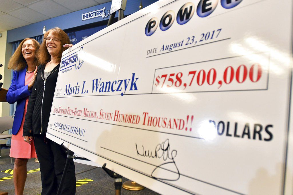 Mavis Wanczyk stands by a poster of her winnings during a news conference where she claimed the $758.7 million Powerball prize at Massachusetts State Lottery headquarters, Thursday, Aug. 24, 2017.   AP Photo