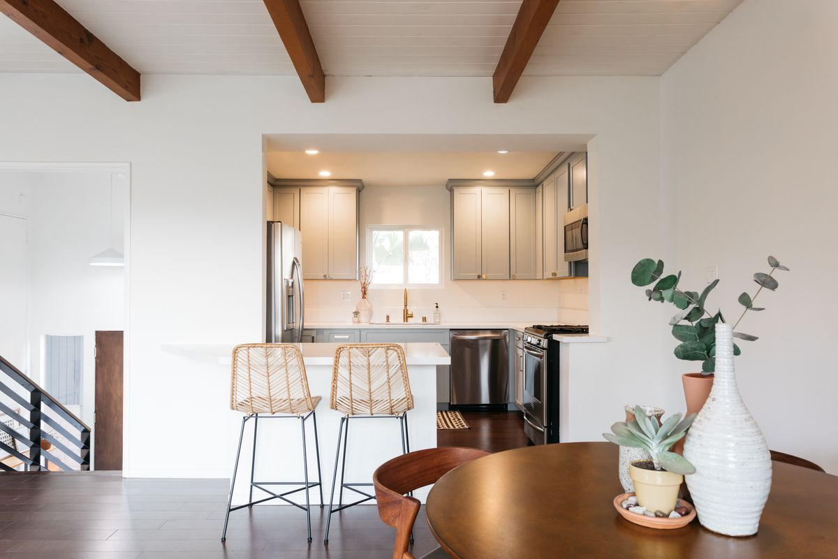 Two bar seats near a kitchen with gray cabinets and stainless steel appliances.