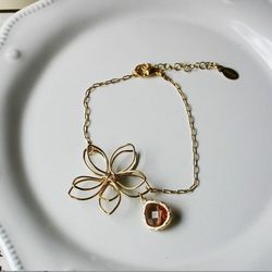 "<a href=""http://www.scarletfiorella.com/index.php/Womens-Accessories/Rebecca-Flower-Bracelet-with-Gem.html"">Flower and Gem Bracelet</a> ($30) at Midtown's Scarlet Fiorella."
