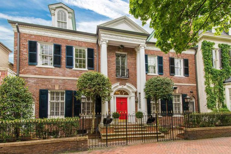 A house in Washington D.C. The facade is red brick and there is a red door with white columns.
