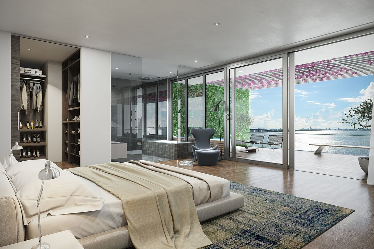 A modern bedroom overlooking the bay with a large walk-in closet, neutral colors, and a huge sliding glass door opening to the stunning balcony