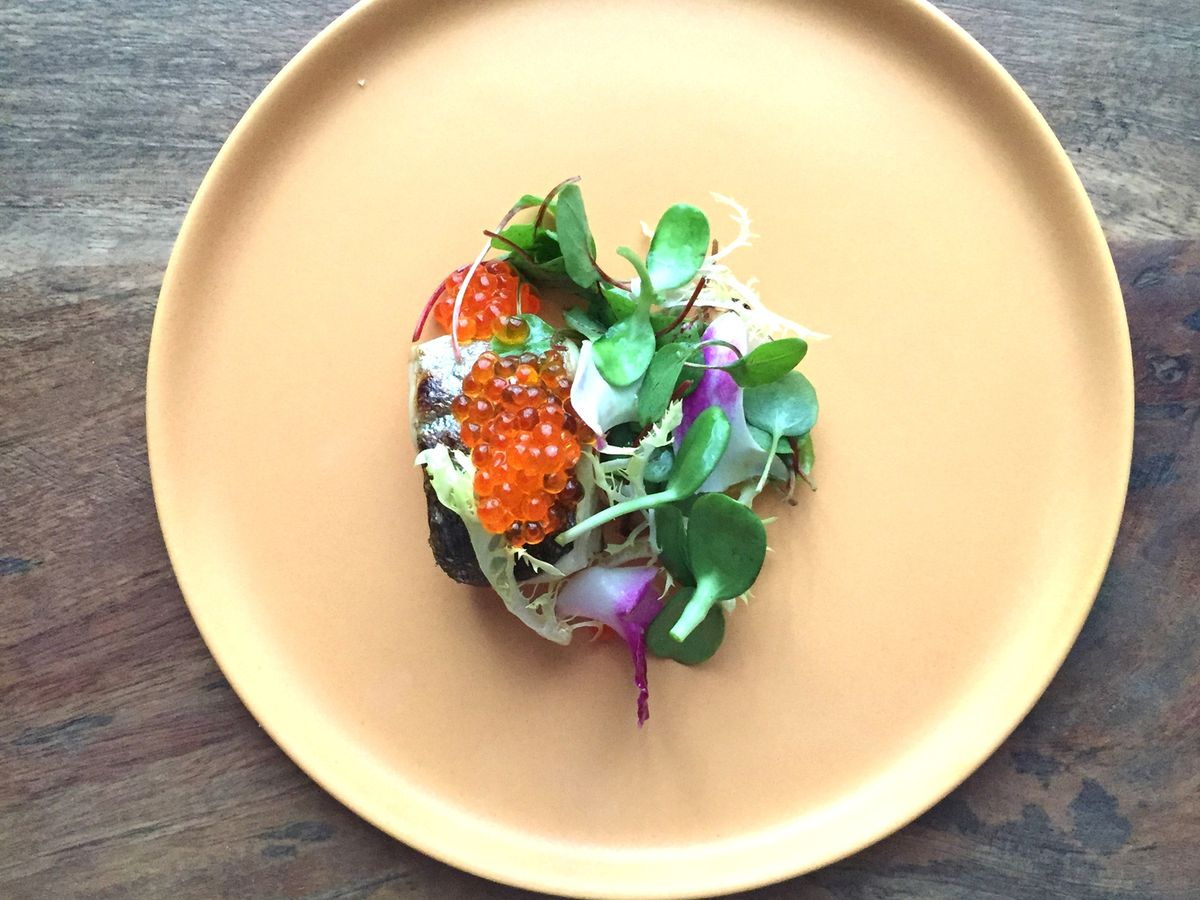 A round yellow plate holds a delicate green salad topped with orange roe