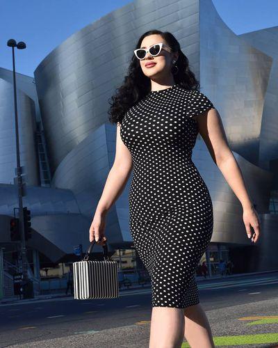A model in a vintage polka dot dress walking down the street