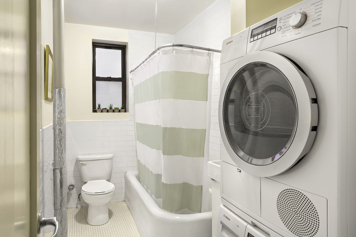 A bathroom with a small bathtub and a washer and dryer.