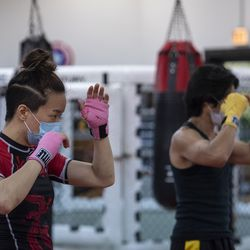 Lan Phan, left, a student at EFK Martial Arts, 5951 N. Clark St., follows along with owner and head coach Anthony Marquez during a boxing class on the first day of Illinois' Phase 4 reopening, Friday, June 26, 2020.