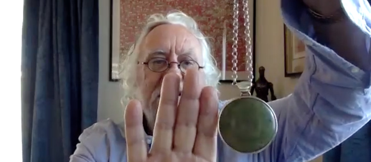 Dan Hennah holds up a round pendant on the end of a bulky chain, next to his hand to show scale. The green stone set in it is larger than the first two knuckles of his pointer finger.