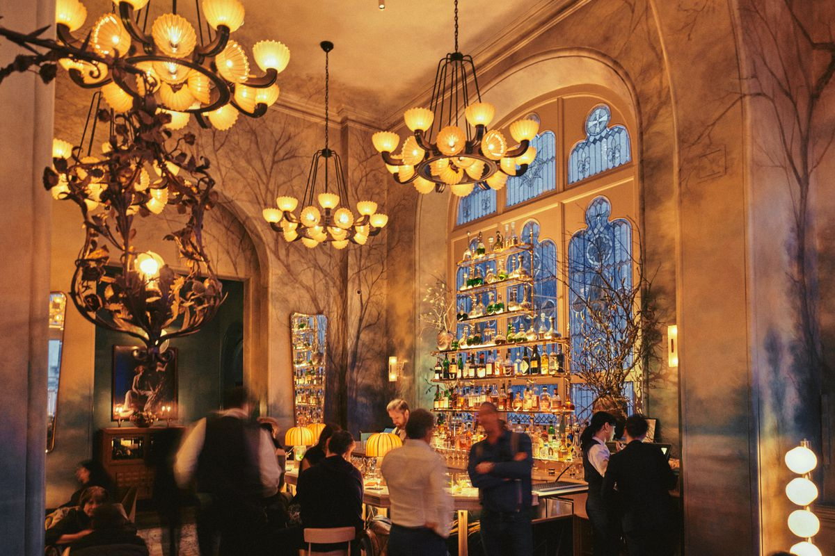 A high-ceilinged room with an amber glow, chandeliers, and people at a bar.