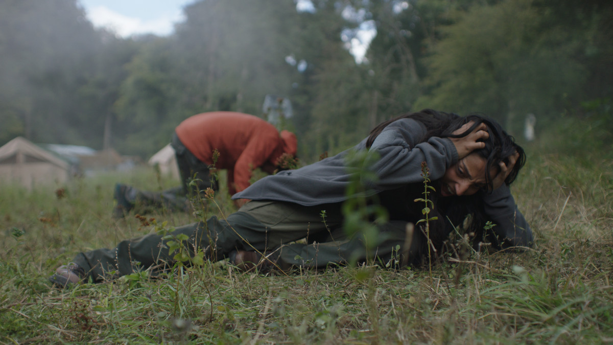 Ellora Torchia and Joel Fry lie in the grass, screaming and covering their ears, in In the Earth