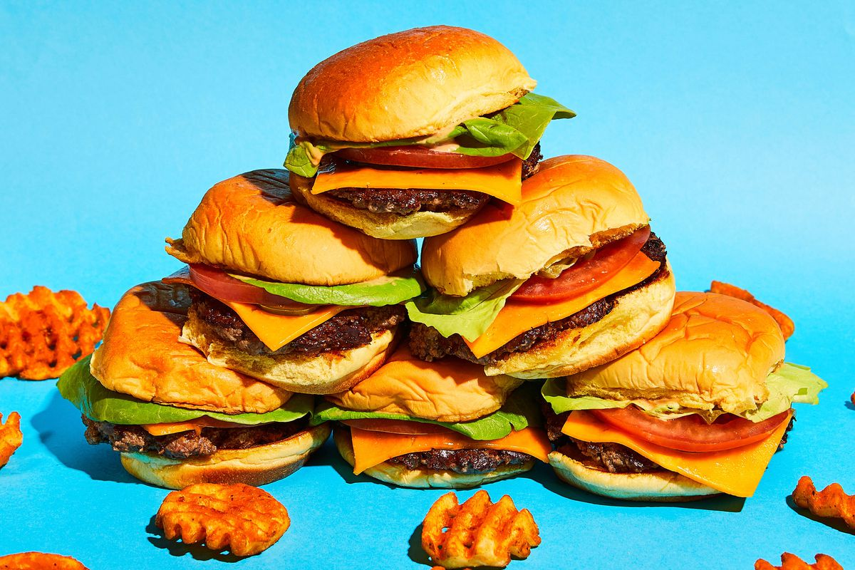 A stack of six cheeseburgers is surrounded by waffle fries against a baby blue backdrop