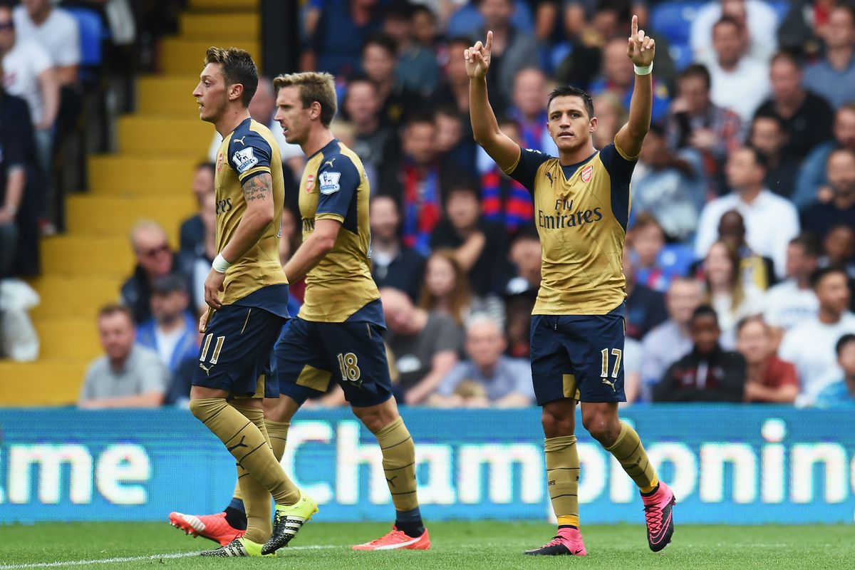 Alexis celebrates his goal. (Well, the own-goal he created, at least.)