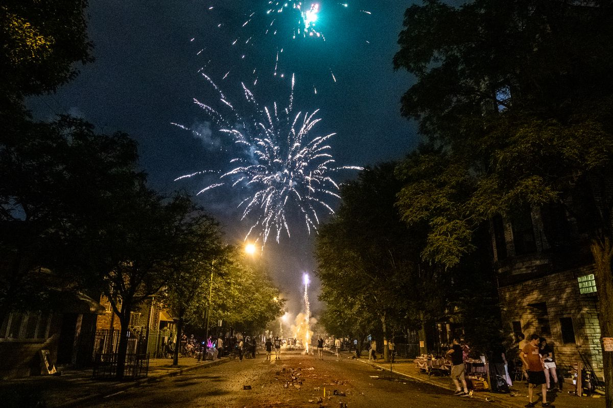 People watch as a firework goes off at a Fourth of July block party in the Pilsen neighborhood, Thursday, July 4, 2019, in Chicago.