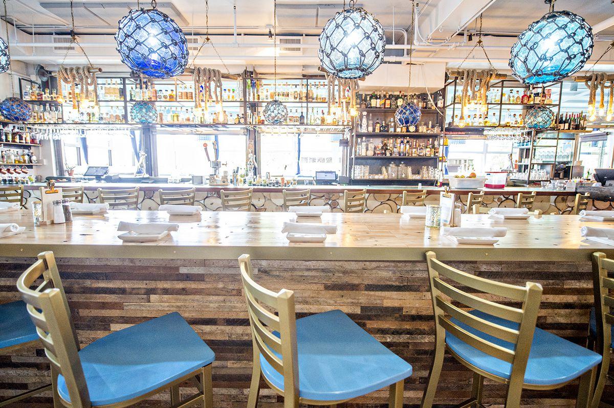 A view across the 14-top table toward the bar at Lola Coastal Mexican.