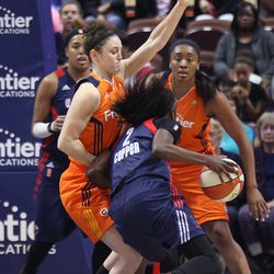Connecticut Sun's Kelly Faris (34) tries to prevent Washington Mystics' Kahleah Cooper (2) from getting to the basket.