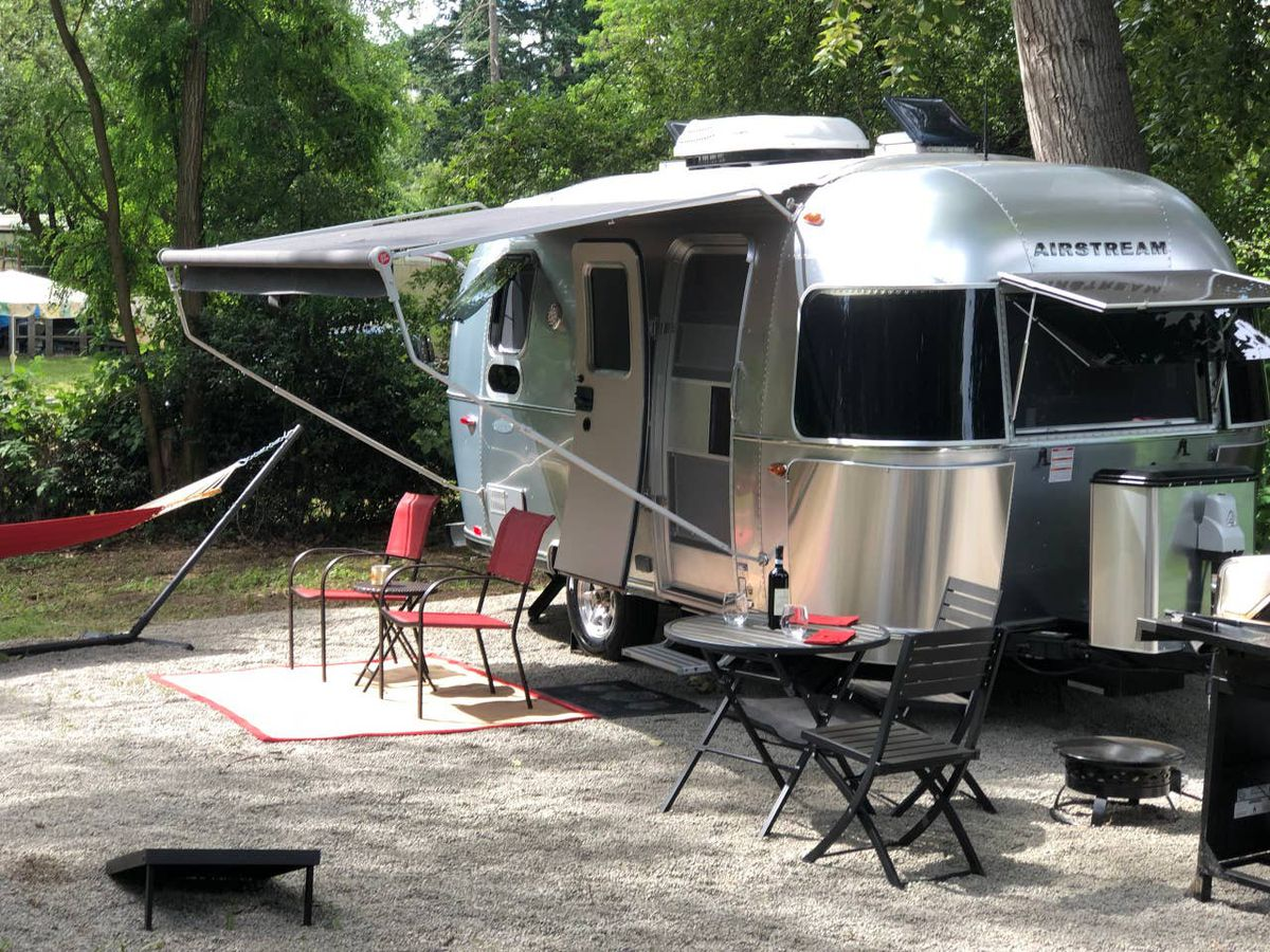 A shiny metal camping trailer with a rounded body has a canopy open to the left over a patio with chairs, tables, and a free-standing hammock. Large evergreen trees are in the background.