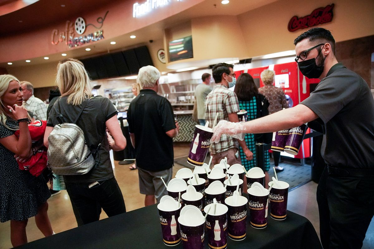 TJ Hewitt places more soda cups on a table for patrons attending a private screening at the Megaplex Theatres at Legacy Crossing in Centerville on Friday, May 29, 2020.