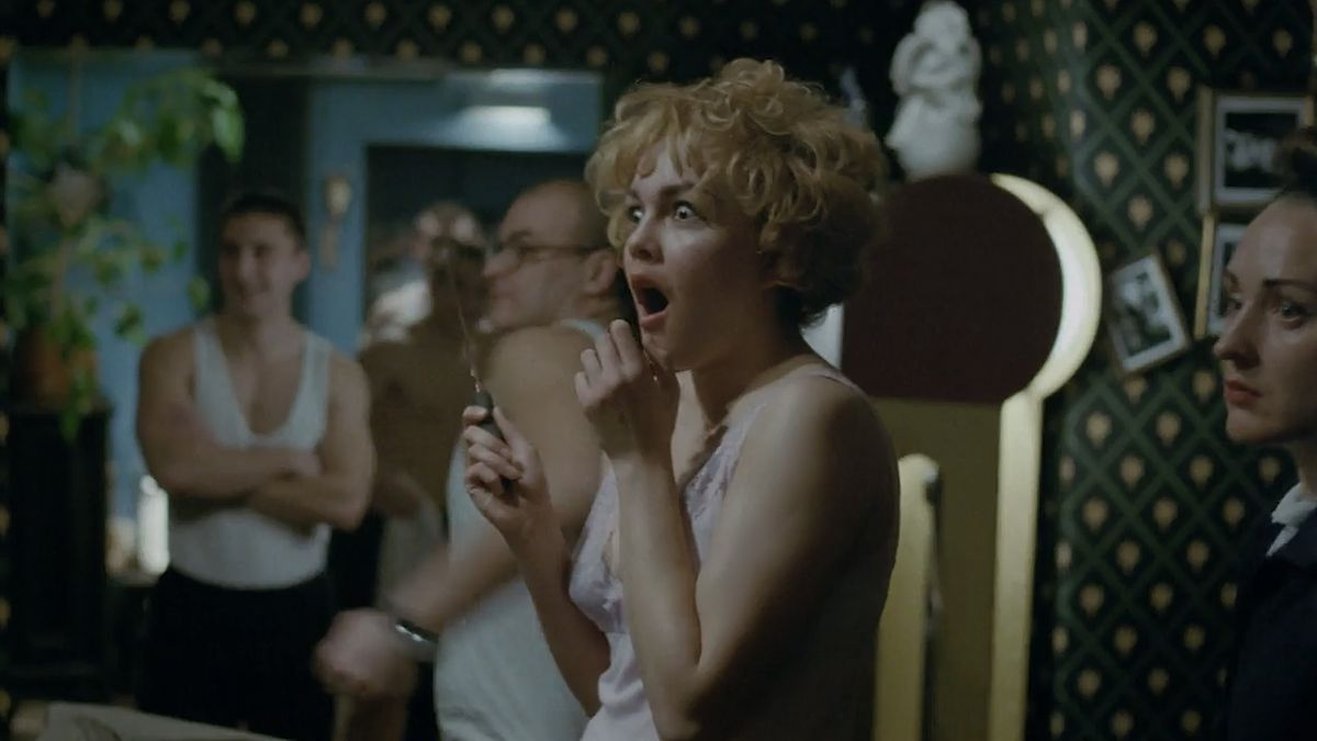 A woman in a pink chemise, clutching a knife in one hand, opens her eyes and mouth wide in shock at something offscreen, as two men in sleeveless white T-shirts in the background also look with seeming amusement at the same thing.