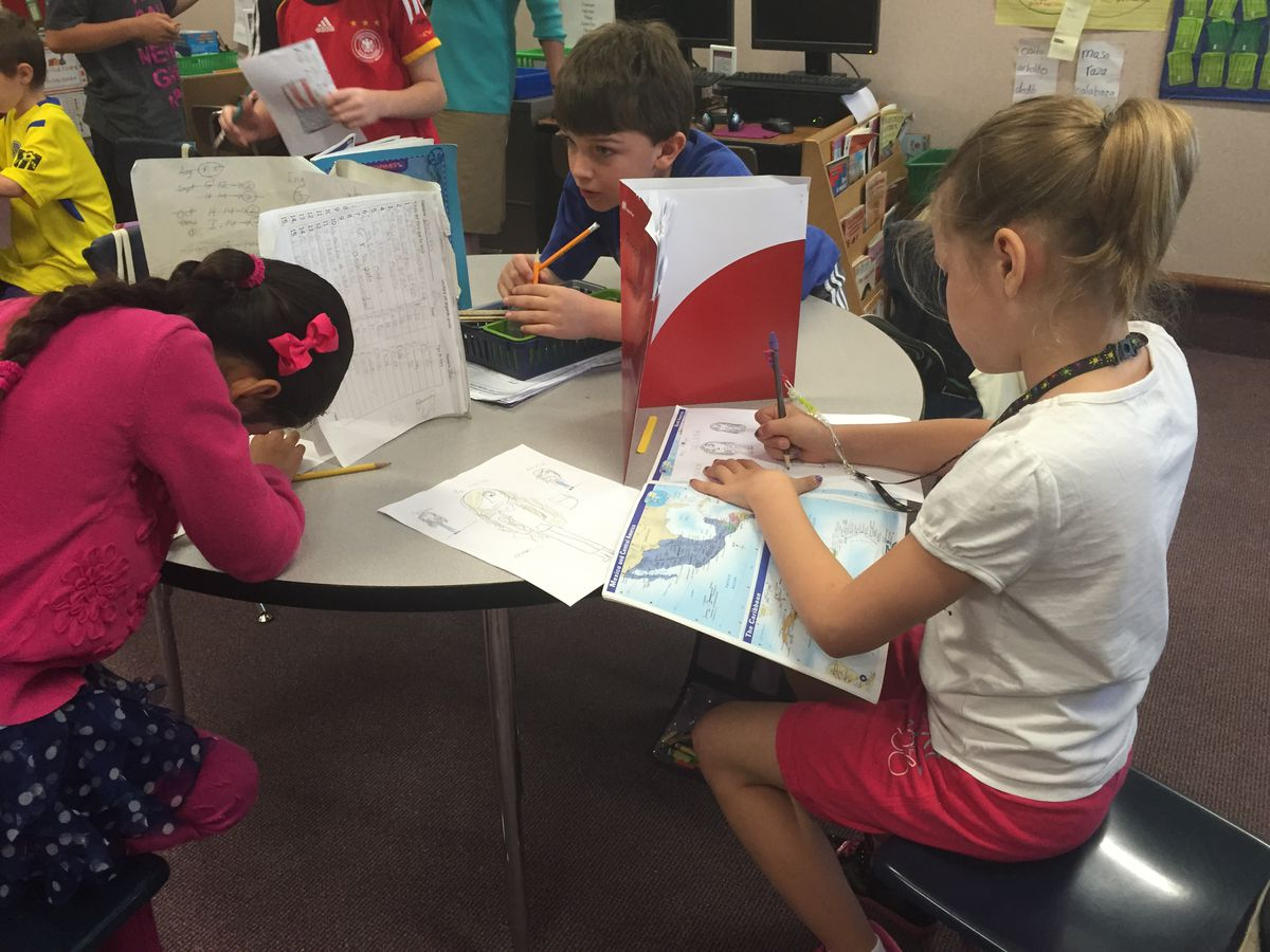 Three girls in Mabel Ramos' third grade class at Forest Glen Elementary School work on writing letters to students in Cuba. Immersion classes are primarily taught in Spanish.