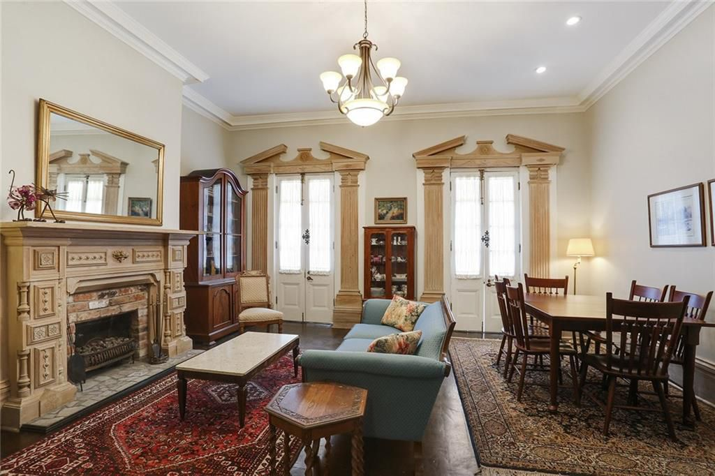 A library-like den has two massive Persian rugs in front of a large blonde-colored fireplace mantel on the left, with two matching French door windows on the wall.