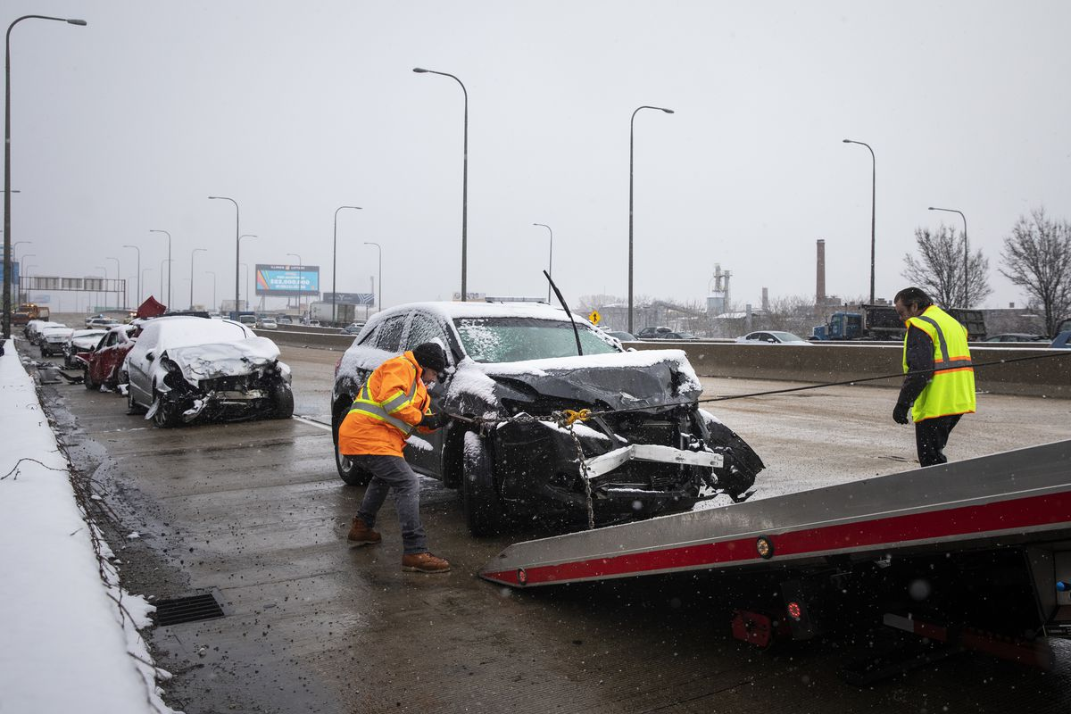S & T Automotive Towing and Repair workers tow a car from the scene of a massive pileup crash involving nearly 60 vehicles, sending more than a dozen people to hospitals, in the inbound lanes of the Kennedy Expressway near North Avenue, Wednesday morning, April 15, 2020.