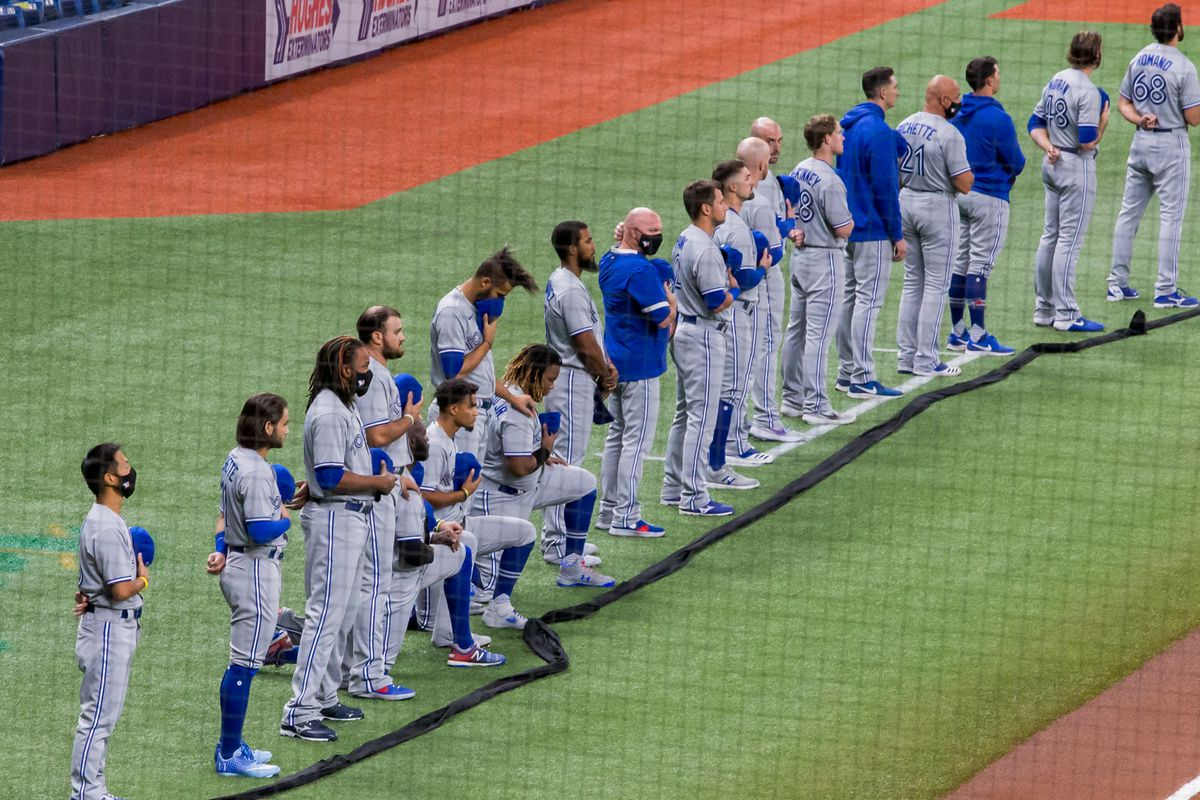 Members of the Toronto Blue Jays wearing grey line up during the National Anthem before opening day at Tropicana Field.