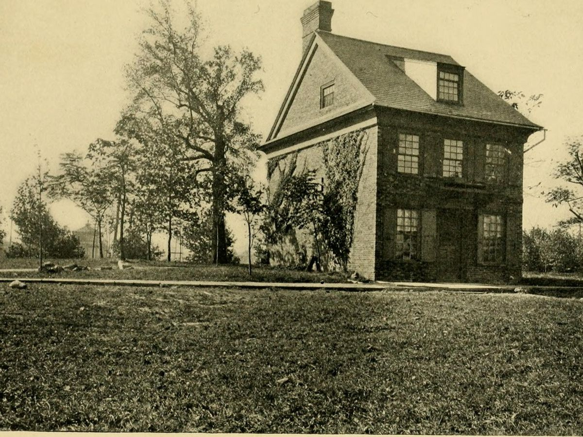 A large house with a lawn in front in Philadelphia. This is an old photograph and is tinted yellow and green.