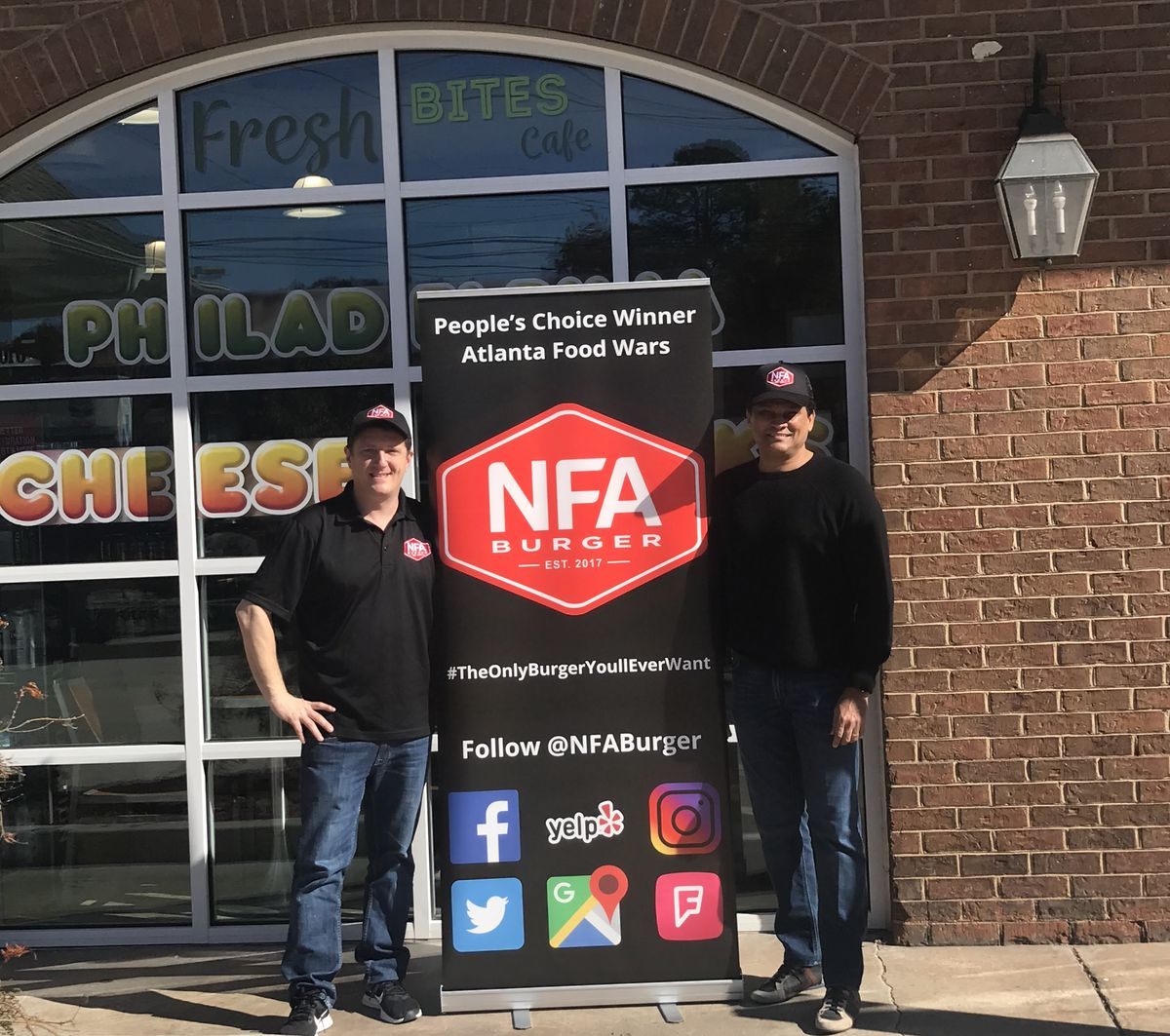 NFA Burger owner Billy Kramer and Chevron owner Salim Thobani standing next to the NFA Burger poster board at the gas station