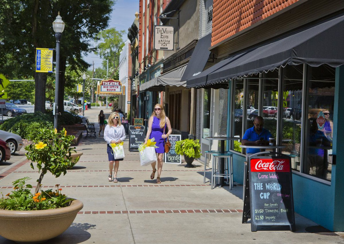 Two women with shopping bags walking down sidewalk in front of stores.