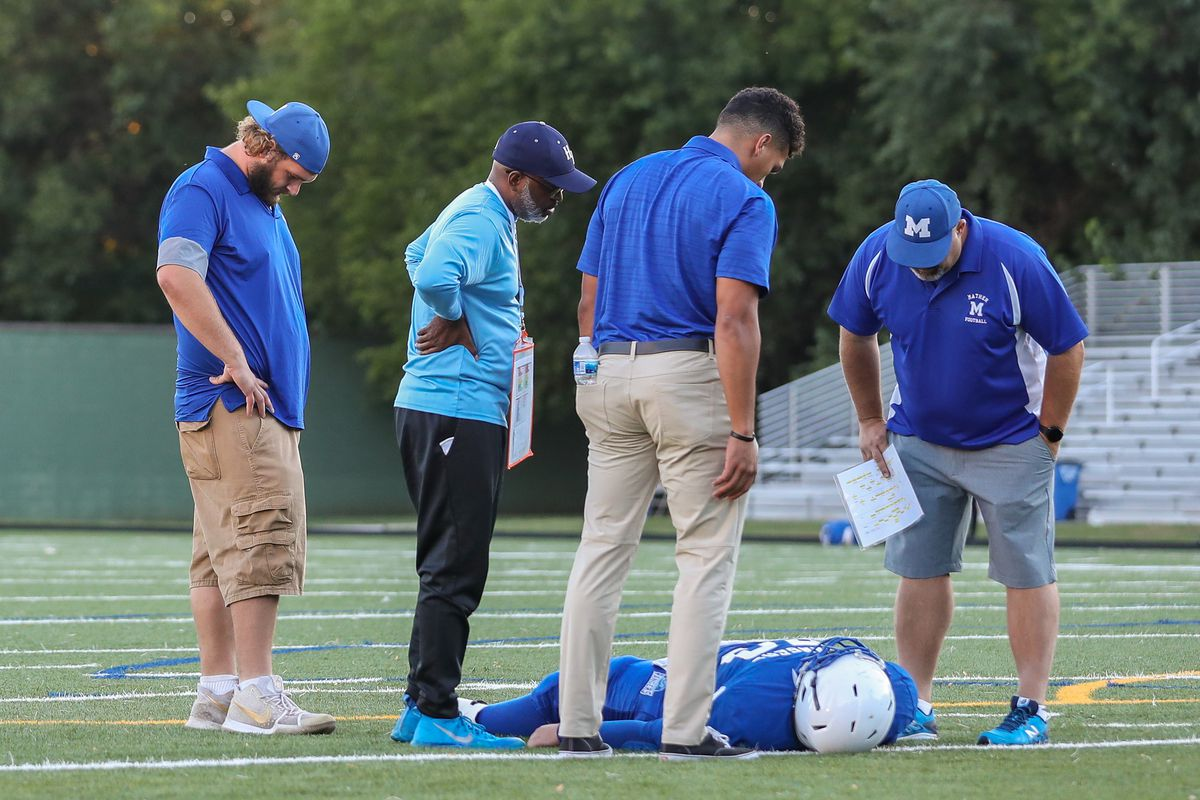 A Mather football player lays injured on the field as coaches and a referee look on during the game against Hyde Park.