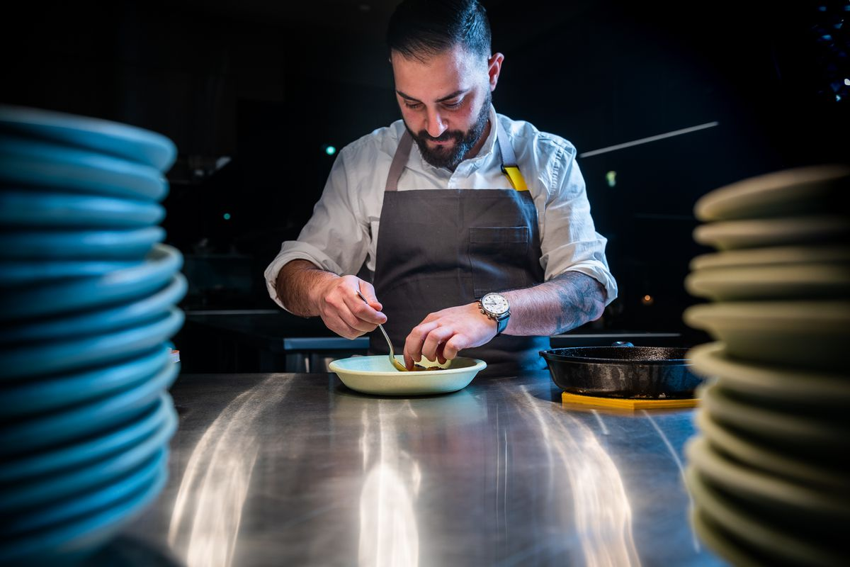 Albi chef-owner Michael Rafidi plates a dish at a metal counter