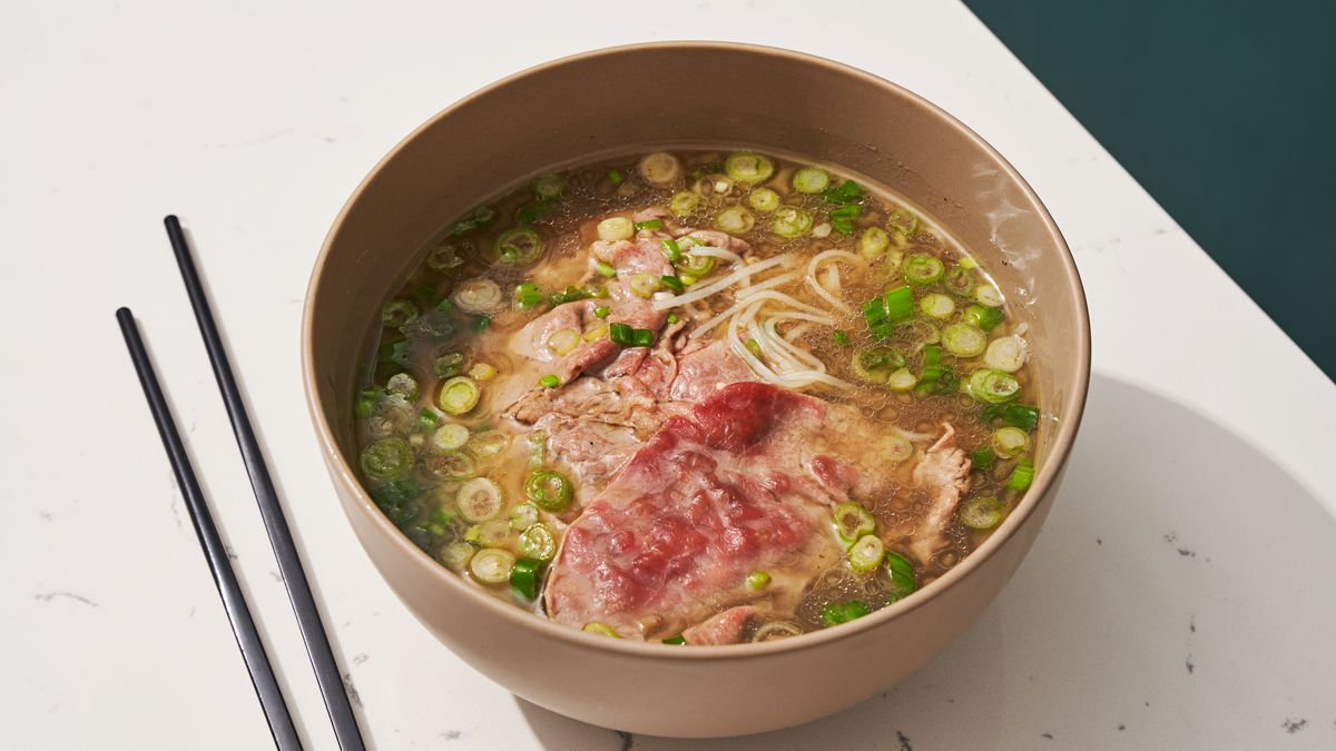 A bowl of pho with sliced scallions, noodles, and partially cooked beef