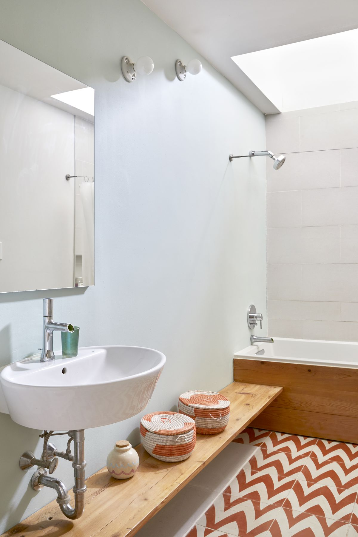 Eggshell-colored bathroom with a low board for storage baskets. A tub sits in the corner.