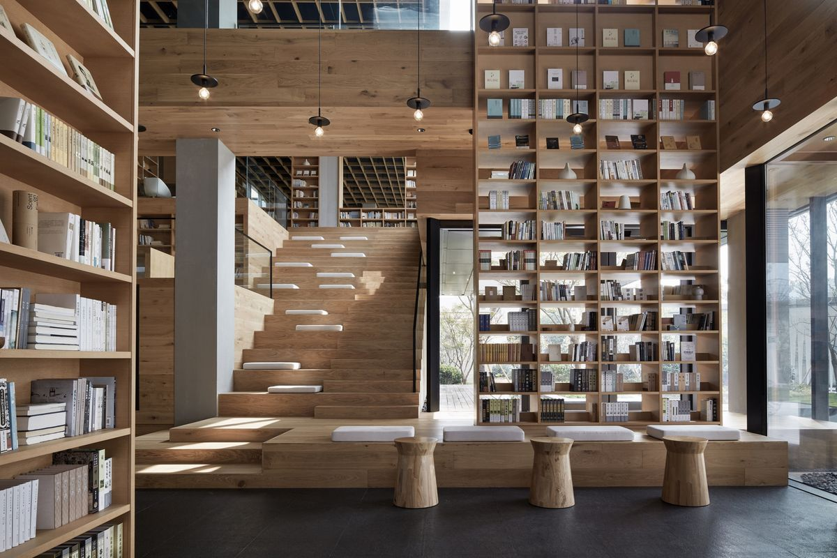 Wooden stairs and shelves contain seating and books.