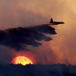FILE -- In this Sept. 12, 2010 file photo, a slurry bomber drops retardant on a burning ridge as the sun sets behind it as a wildfire burns near Loveland, Colo. The West's 2012 wildfire season exploded in earnest last month with a wind-whipped blaze that killed three people in rugged alpine canyon country near Denver. At its peak, it took a 700-strong federal firefighting team a week of labor, day and night, to tame the blaze _ and other states throughout the West took notice. Fire experts say this year's drought, low snowpack and record-high temperatures in much of the West portend a dangerous installment of what has become year-round wildfire threat.