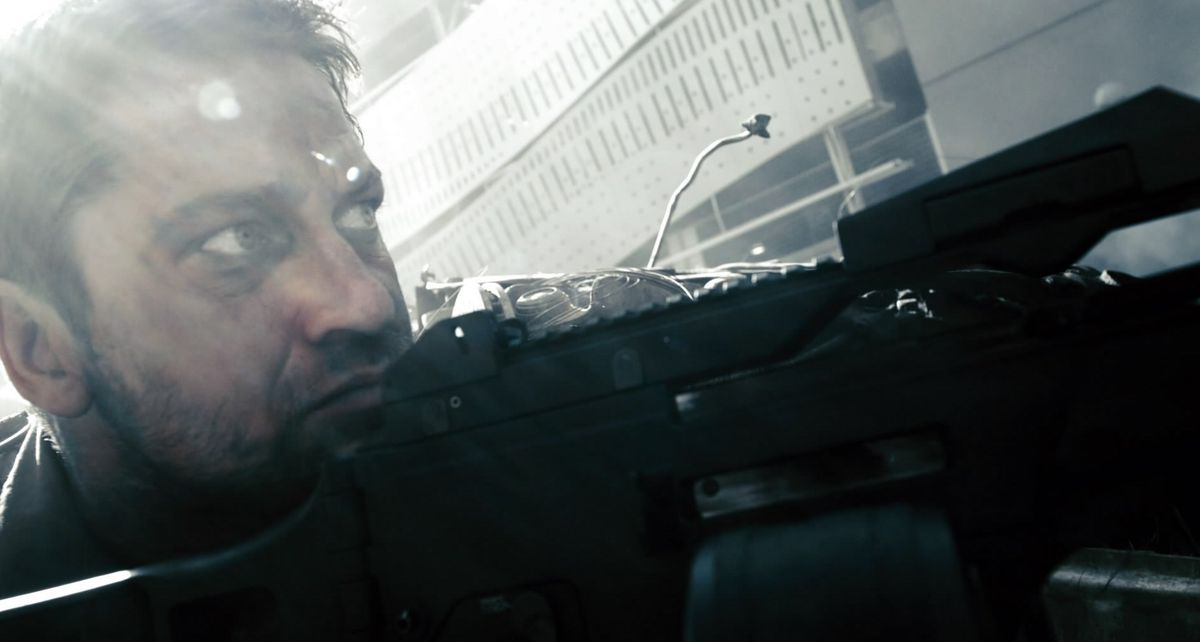 Gerard Butler in Gamer squatting down with a machine gun