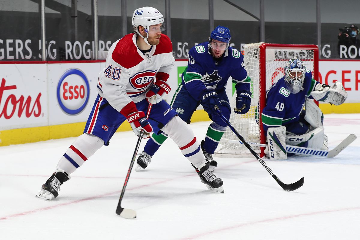 Montreal Canadiens Right Wing Joel Armia (40) plays the puck while watched by Vancouver Canucks Defenceman Quinn Hughes (43) during their NHL game at Rogers Arena on January 20, 2021 in Vancouver, British Columbia, Canada.