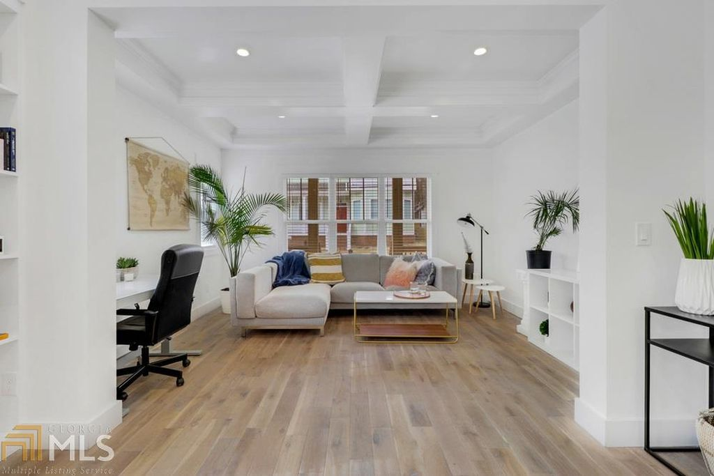 A white room with a couch and wood floors.