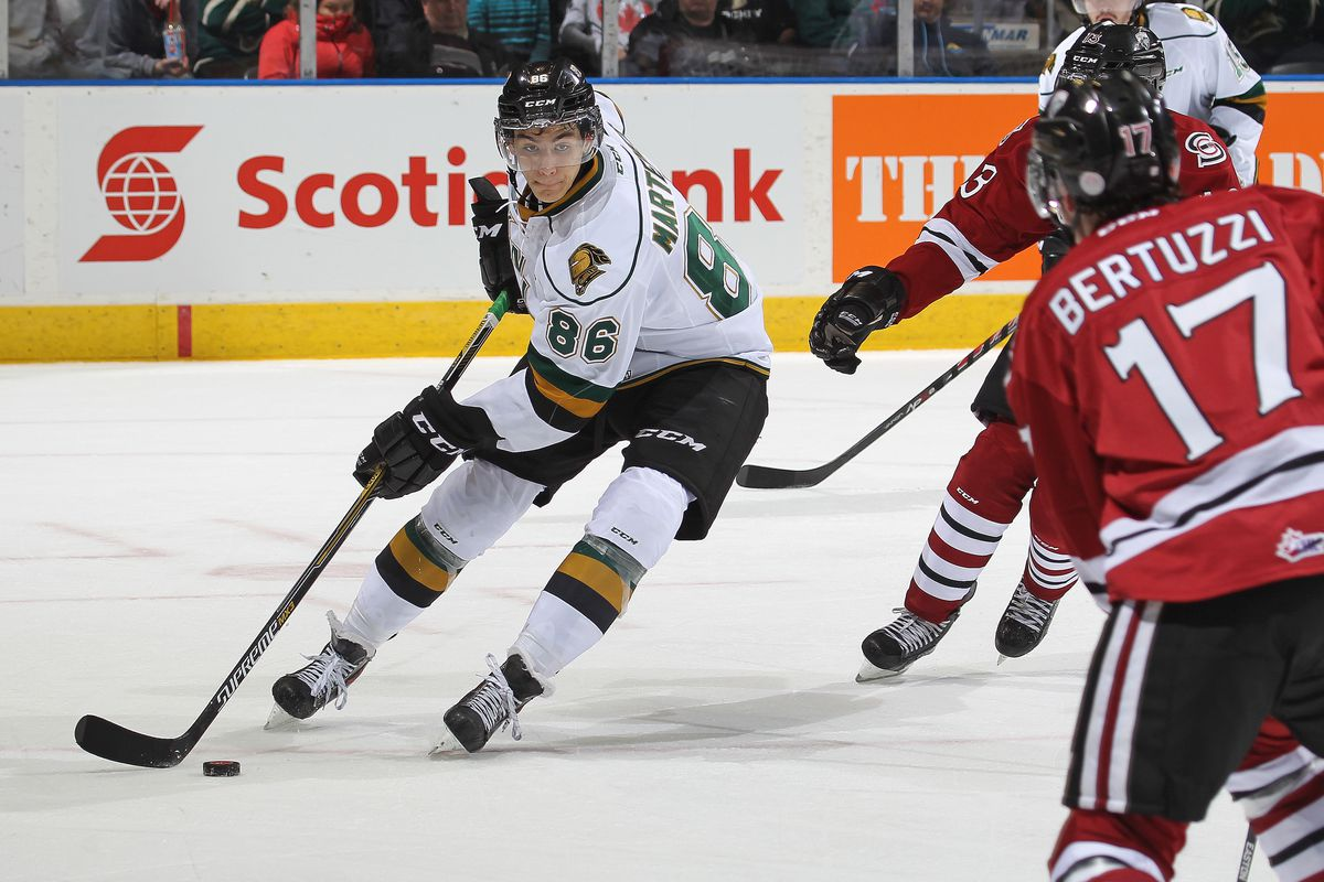 Chris Martenet #86 of the London Knights clears a puck against Tyler Bertuzzi #17 of the Guelph Storm in an OHL game at Budweiser Gardens on November 6, 2014 in London, Ontario, Canada.