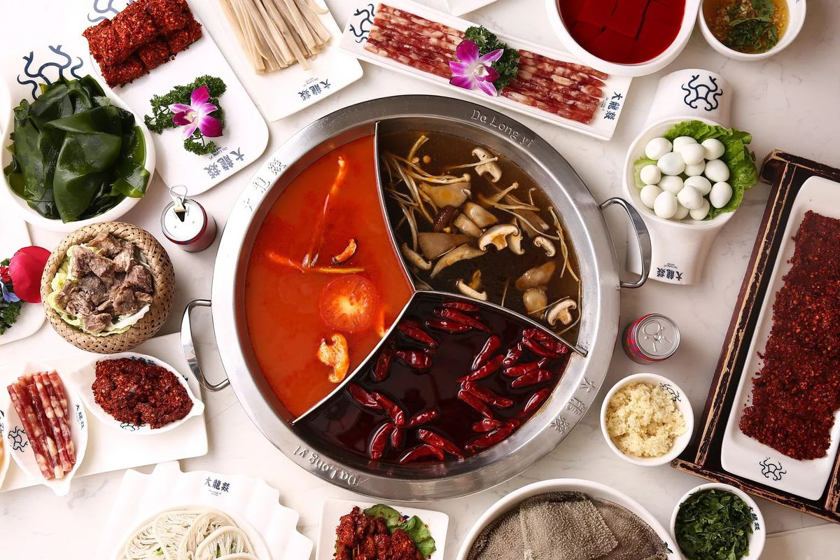 A top-down image of various dishes at Da Long Yi, with hot pot at the center.