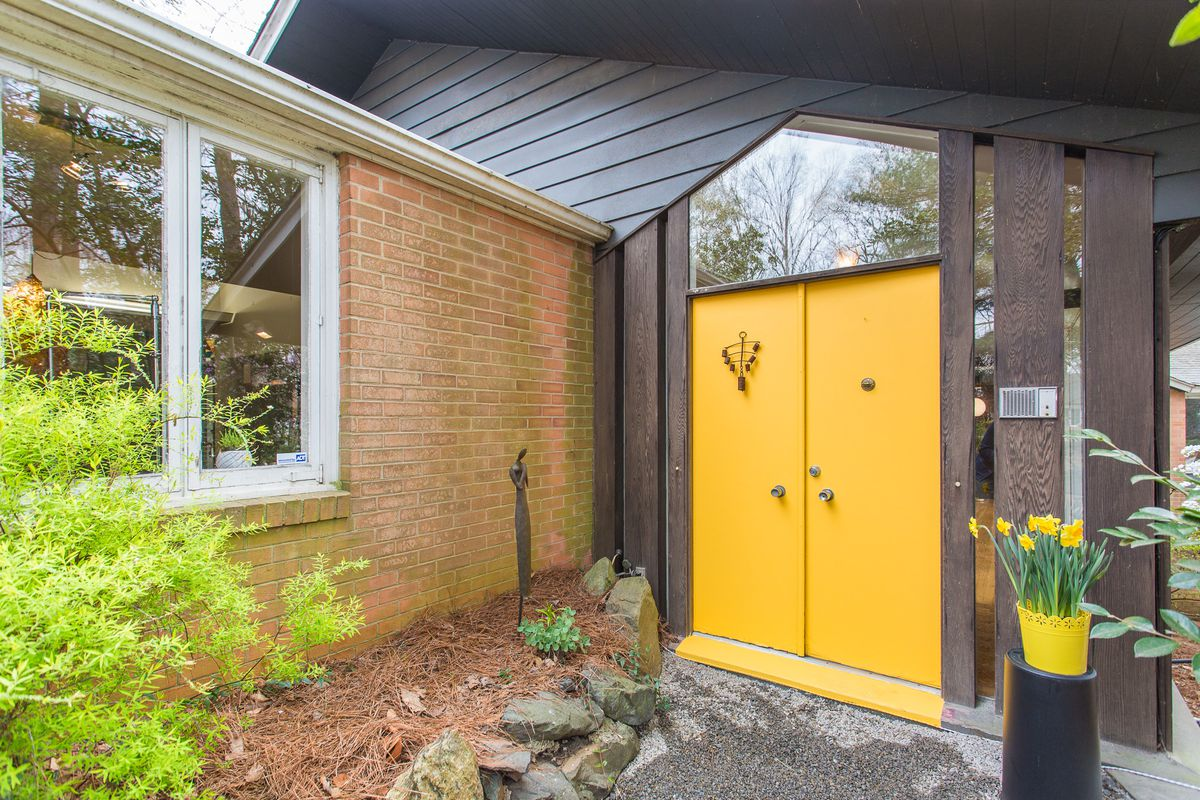 A two-sided bright yellow door sits at the entrance of a midcentury modern house.