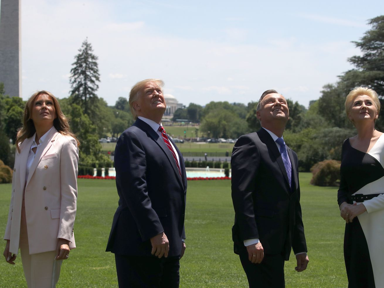 First lady Melania Trump, President Donald Trump, Polish President Andrzej Duda, and first lady of Poland Agata Kornhauser-Duda look up as F-35 fighter jets fly overhead on June 12, 2019.